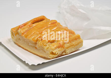 a piece of apple pie on paper plate with paper bag, close up, isolated on white background - Stock Photo