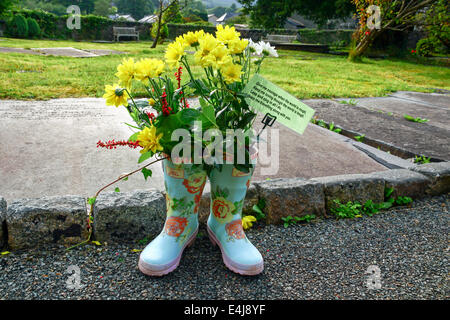 Beddgelert, Wales, UK: Decorated gumboots adorn the churchyard of St Mary's Church during the yearly flower-festival. - Stock Photo