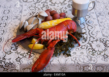 Traditional New England Clambake including lobster, clams, potatoes and corn on the cob on a pewter plate with a - Stock Photo