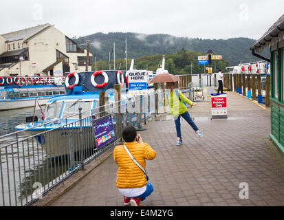 Bowness on Lake Windermere, UK. 14th July, 2014. Tourists making the most of a rainy day Japanese tourists have - Stock Photo