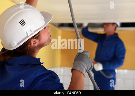 Electricians wiring a large room - Stock Photo