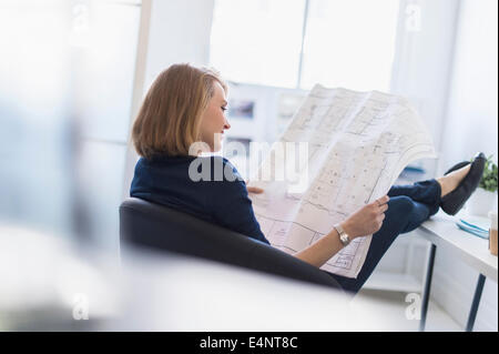 Business woman looking at blueprint in office - Stock Photo