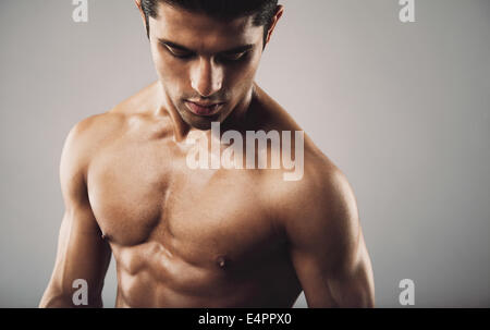 Portrait of fit muscular shirtless man looking down. Hispanic male model on grey background. Workout and fitness - Stock Photo