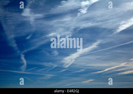 Jet contrails or cirrus aviaticus clouds in clear sky above desert in northern Arizona, USA - Stock Photo