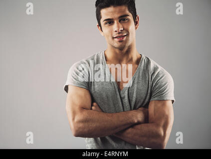 Cropped image of muscular young man standing with his arms crossed against grey background. Macho man posing confidently. - Stock Photo