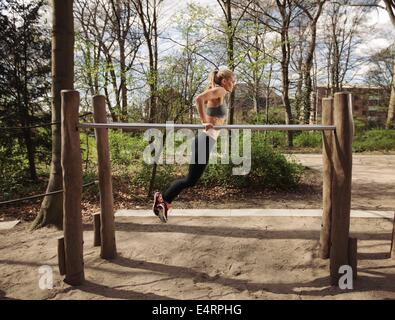 Side view of muscular young woman doing triceps dips on parallel bars at park. Caucasian female fitness model exercising - Stock Photo