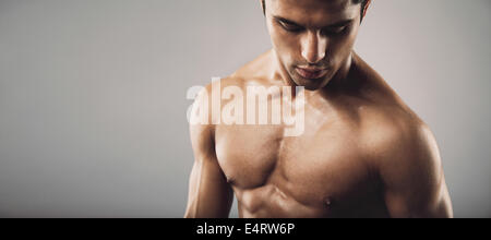 Portrait of fit masculine shirtless man  looking down. Wide panoramic crop with copy space. Workout and fitness - Stock Photo