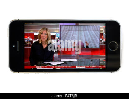 Watching BBC News live via the BBC iPlayer app on an Apple iPhone 5S - Stock Photo