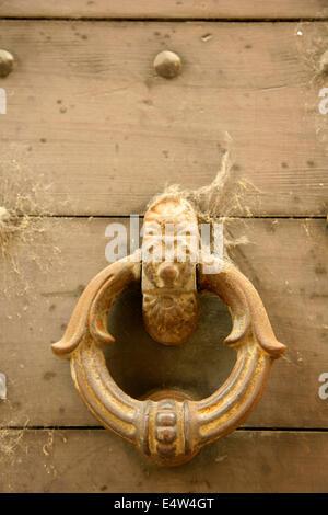 Old metal doorknocker on wooden door, Bergamo, Italy. - Stock Photo