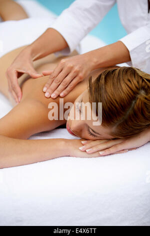 Woman receiving a poolside back massage - Stock Photo