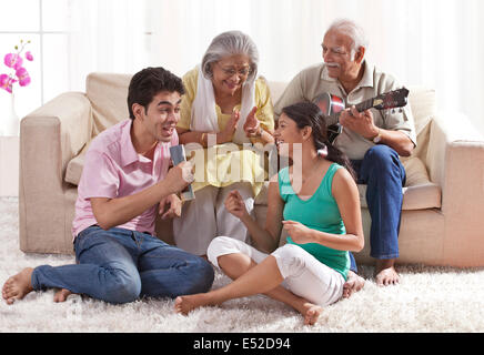 Grandfather playing the guitar with grandmother and grandchildren singing - Stock Photo