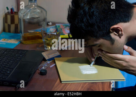 Headshot of man snorting cocaine at home - Stock Photo