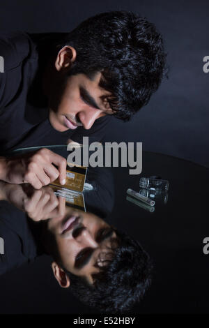 Young man cutting cocaine lines with credit card on mirror - Stock Photo