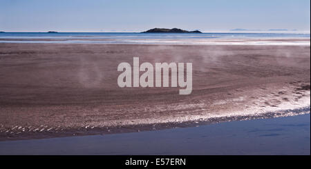 Panoramic view of steam rising from the sand as the morning sun heats the beach - Stock Photo