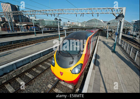 A Virgin Class 390 Pendolino train in the platform of Manchester Piccadilly Rail Station. - Stock Photo