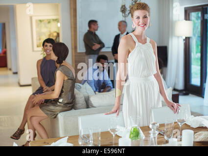Woman smiling at table at party - Stock Photo