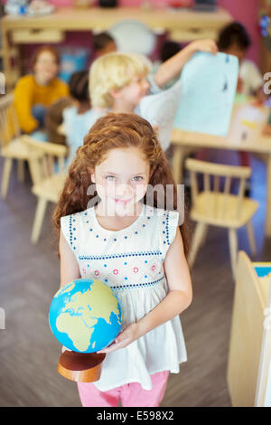 Student holding globe in classroom - Stock Photo