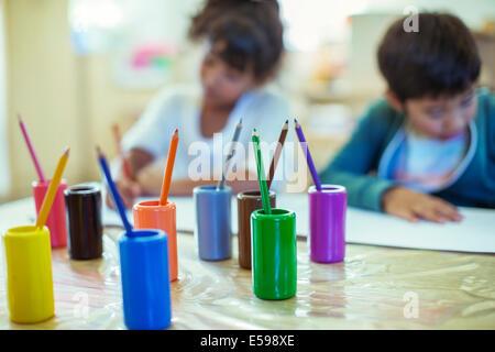 Colored pencils on desk in classroom - Stock Photo