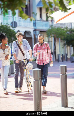 Friends walking together on city street - Stock Photo