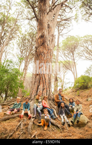 Students and teachers sitting on tree in forest - Stock Photo