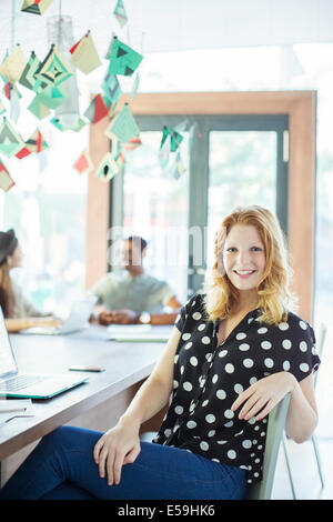 Woman smiling at conference table in office - Stock Photo