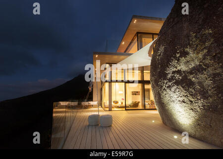 Illuminated modern house with rock feature and balcony - Stock Photo