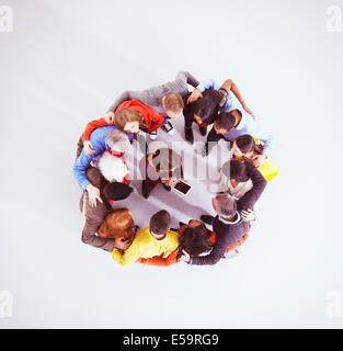 Business people huddled around woman with digital tablet - Stock Photo