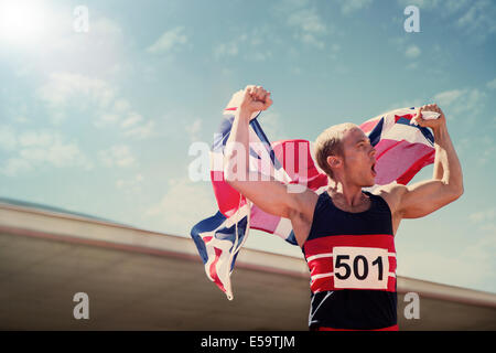 Track and field athlete holding British flag - Stock Photo