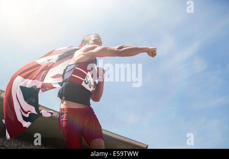 Track and field athlete cheering with British flag - Stock Photo