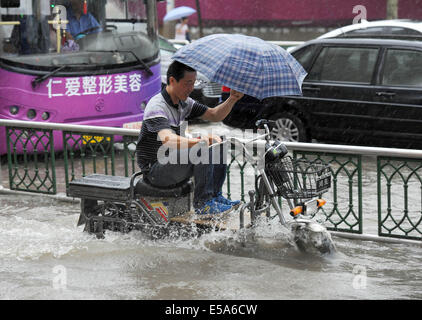 Huai'an, China's Jiangsu Province. 25th July, 2014. A man rides an electronic scooter along a waterlogged road in - Stock Photo