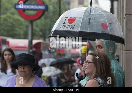 July 25, 2014 - London, London, UK - Tourists take cover at the entrance to Westminster tube station as a storm - Stock Photo