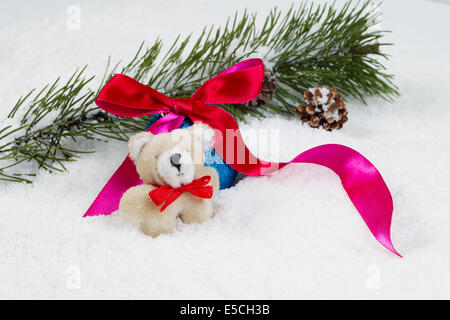Closeup front view of small fur bear with snow covered fir branch, red ribbon and pine cones in background - Stock Photo