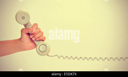 a man hand holding the handset of a telephone, with a retro effect - Stock Photo