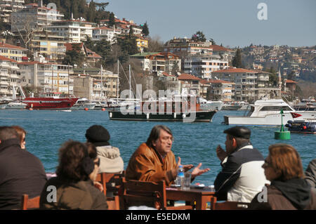 People enjoy a Sunday morning in March at the terrace of a cafe on the European shore of the Bosphorus in Bebek, - Stock Photo