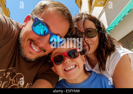 Family having fun wearing sunglasses & waving to a camera taking selfie photograph on summer holiday - Stock Photo