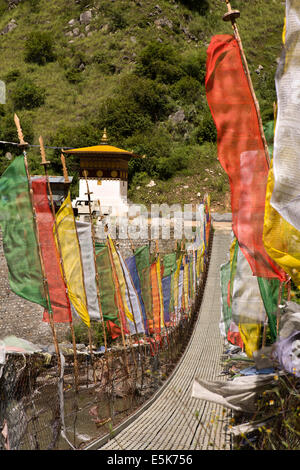 Eastern Bhutan, prayer flags lining suspension footbridge across Kuri Chhu River - Stock Photo