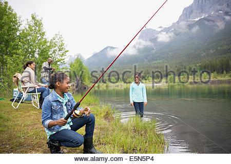 Family fishing at lakeside below mountains - Stock Photo