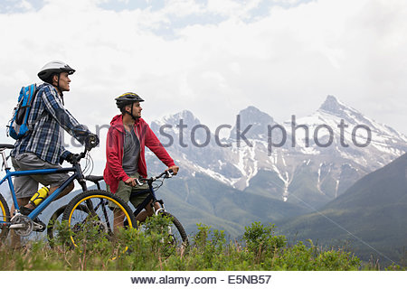 Men on mountain bikes looking up at mountains - Stock Photo