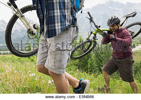 Men carrying mountain bikes up grassy hill - Stock Photo