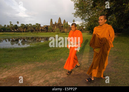Two Buddhist monks on the outside of the Temple of Angkor Wat. The plan of Angkor Wat is difficult to grasp when - Stock Photo