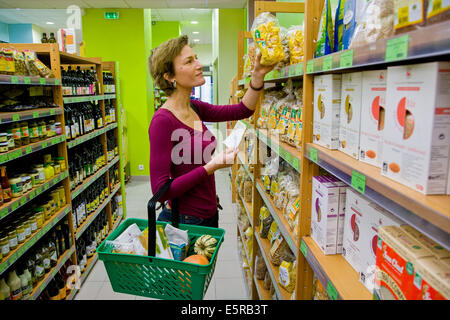 Woman grocery shopping in bio supermarket. - Stock Photo