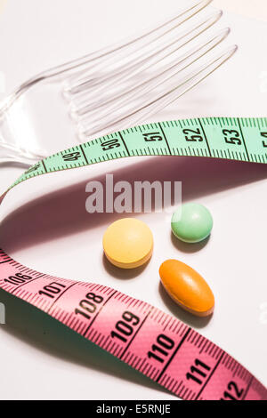 Slimming pills and measuring tape. - Stock Photo