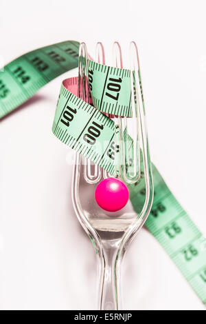 Slimming pink pill and measuring tape coiled on fork. - Stock Photo