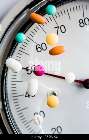 Slimming pills on weight scale. - Stock Photo