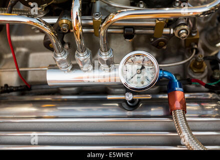 Engine compartment of antique hot rod car with focus on pressure gauge on oil piping on the engine block - Stock Photo