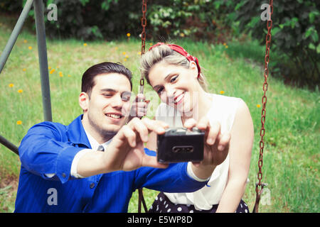 Young vintage couple taking selfie camera in garden - Stock Photo