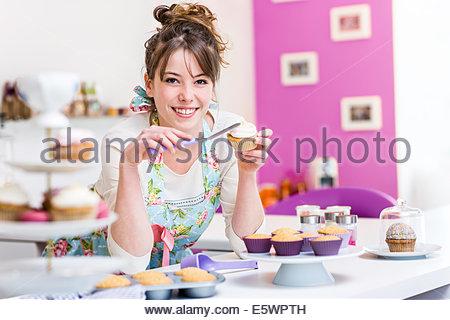 Woman decorating cupcake - Stock Photo