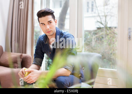 Young man having coffee in living room - Stock Photo