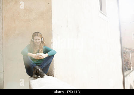 Young woman sitting cross legged listening to music through headphones - Stock Photo