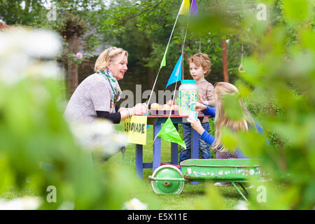 Grandmother buying lemonade from grandchildren's stand - Stock Photo